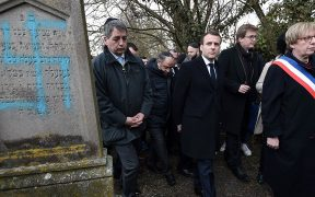 President Emmanuel Macron, center, visits a vandalized Jewish cemetery in Quatzenheim, France, on Feb. 19, a day of nationwide marches against a rise in anti-Semitic attacks. (Frederick Florin/AFP/Getty Images)